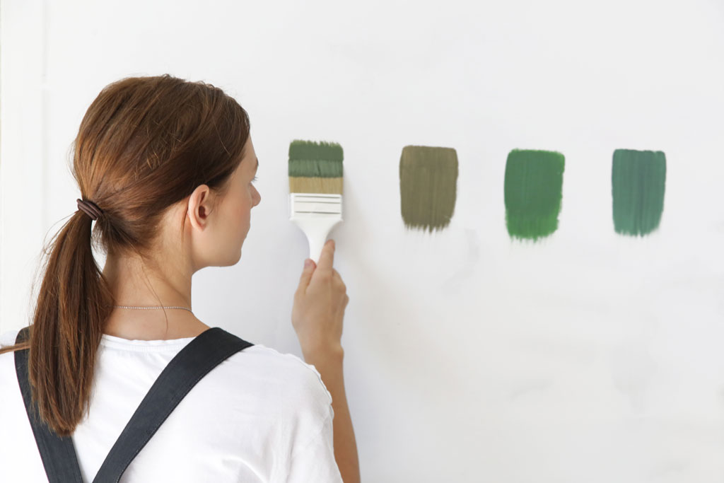 pIcking between 4 green paint colors by painting swatches on the wall